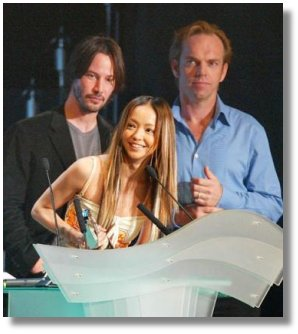Japanese pop singer Namie Amuro smiles after receiving the 'Best Collaboration' award as presenters Keanu Reeves, left in background, and Hugo Weaving look on during the MTV Video Music Awards Japan 2003 in Saitama, near Tokyo, Sunday, May 25, 2003. (AP Photo/Shizuo Kambayashi)